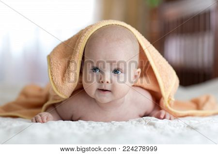 Smiling baby covered soft towel. Cute child lying on bed after bathing or shower in living room