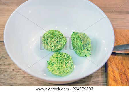 Close up pieces of butter mixed with green herbs in white bowl, healthy food concept