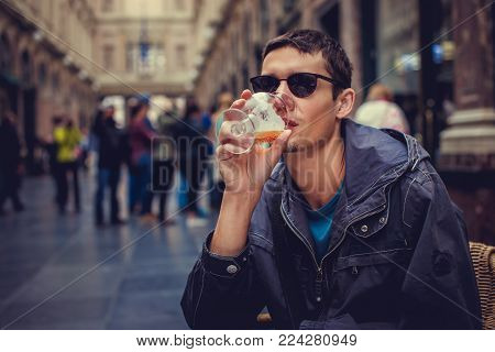 A man in sunglasses drinking beer in a public place.