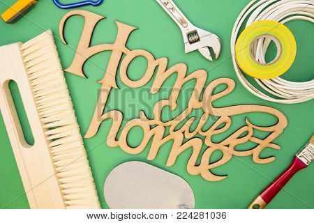 Home, House Repair, Redecorating, Renovating Concept. Home Sweet Home inscription with a set of repairing tools, green background with copy space, top view, flat lay