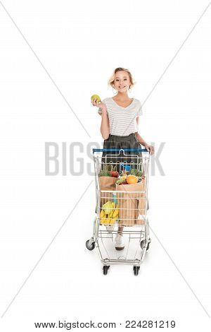 beautiful young woman holding apple and smiling at camera while standing with shopping trolley with grocery bags isolated on white