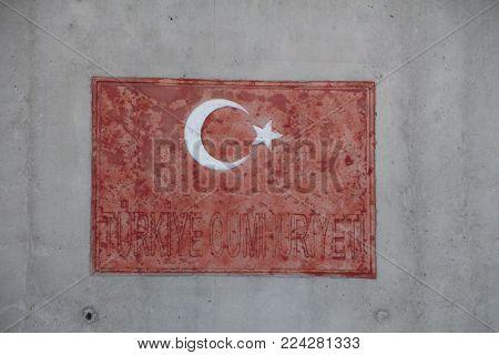 Red turkish flag on the wall. Flag on concrete. Sanliurfa, Ceylanpinar,