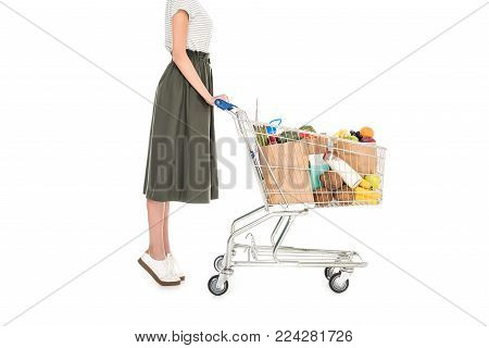 side view of woman standing with shopping trolley with paper bags and grocery isolated on white