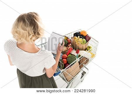 high angle view of young woman holding blank notebook and shopping trolley with grocery bags isolated on white
