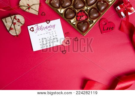 Delicious chocolate candies in gift box with calendar on a red background. Greeting card for Mother's Day, 8 March, Birthday, Valentines Day copy space flat lay