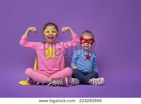 Little children are playing superhero. Kids on the background of bright ultra violet wall. Girl power concept. Yellow, pink, blue, red and purple colors.
