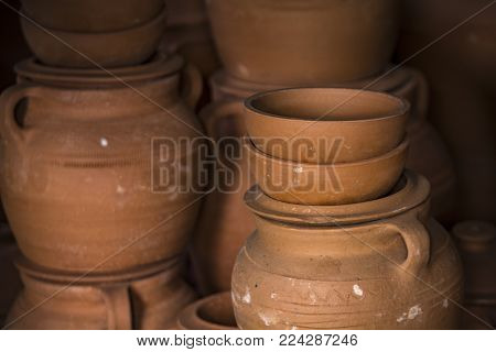 Many clay dishes stacked for sale, pots and bowls alike