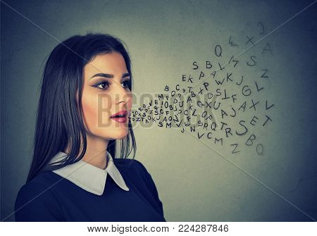 Woman talking with alphabet letters coming out of her mouth. Communication, information, intelligence concept