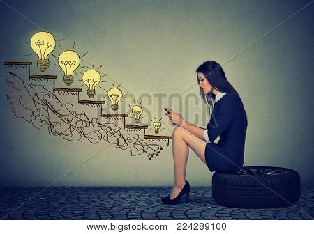 Happy young woman sitting on a wheel in front of growing up light bulbs. Business education success, promotion, company growth concept. Businesswoman using mobile phone