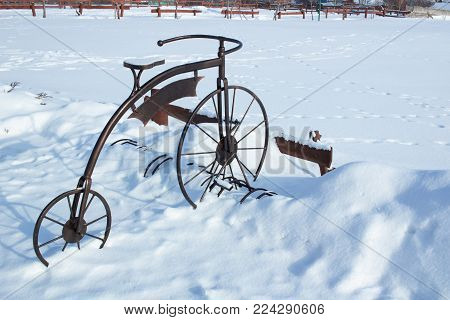 Iron sculpture of bicycle in white snow on wintertime