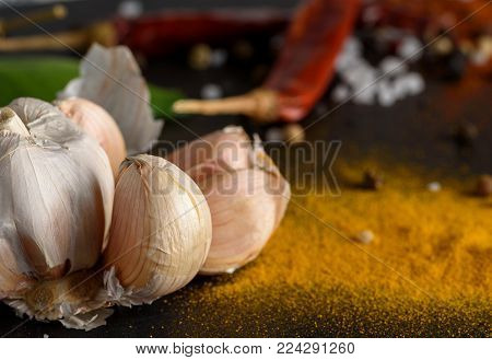 Fresh garlic and spices on black stone background