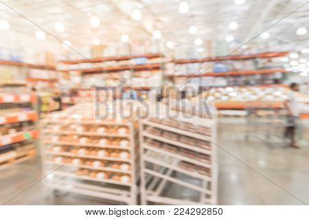 Blurred variety of cakes, cookies and desserts on display rack at bakery section in wholesale store in America. Selection item of trays in bakery aisle at warehouse club. poster