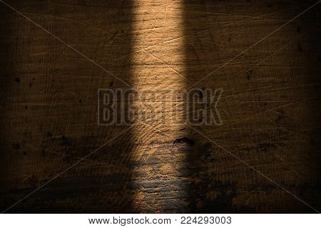 Weathered and distressed wooden board background with downward incoming light streak. old wood background.