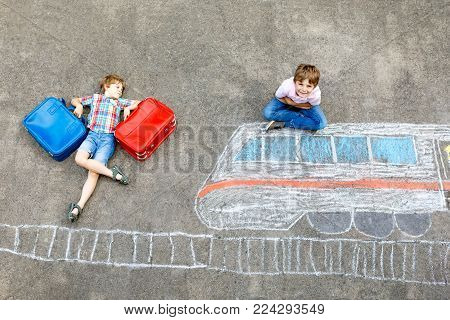 Two little kids boys having fun with train picture drawing with colorful chalks on asphalt. Children having fun with chalk and crayon painting. going on vacations and travel. Friends with suitcases.