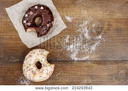 Two bitten donuts with glaze and chocolate on a dark wooden surface top view copy space. American National Donut Day.