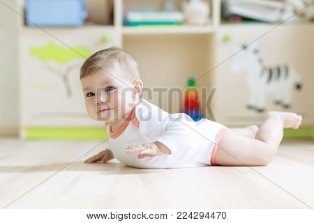 Cute baby girl learning crawling and sitting in children room at home. New born child, little girl lying on belly. Family, new life, childhood, beginning concept.