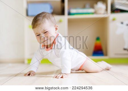 Cute sad crying baby on ground in kids room. New born child, little girl looking at the camera and crawling. Family, new life, childhood, beginning concept. Baby with tears