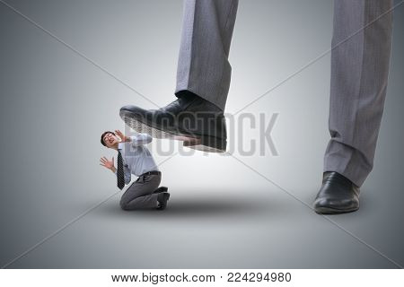 Bad angry boss stamping on employee in business concept