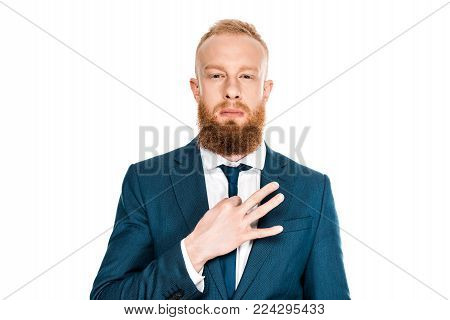 serious bearded businessman adjusting necktie and looking at camera isolated on white