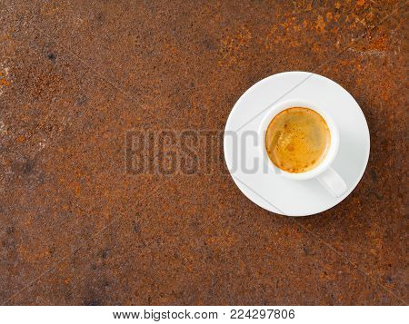 black frothy coffee with foam in white cup with plate on rusty metal table, top view, empty space for text