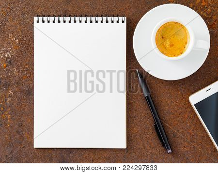 clean white sheet in an open spiral-bound pad, pen, mobile phone and Cup of coffee on the iron of the rusty metal table, top view
