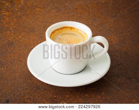 black frothy coffee with foam in white cup with plate on  rusty metal table, side view