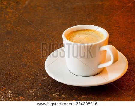 black frothy coffee with foam in white cup with plate on  rusty metal table, warm lamp light of coffee shop, side view, empty space for text