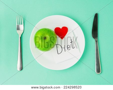 Ripe raw juicy green Apple, red heart, slip of paper with inscription diet on a white plate, fork, knife on a bright turquoise blue colour table, top view. Diet for heart health as a lifestyle.