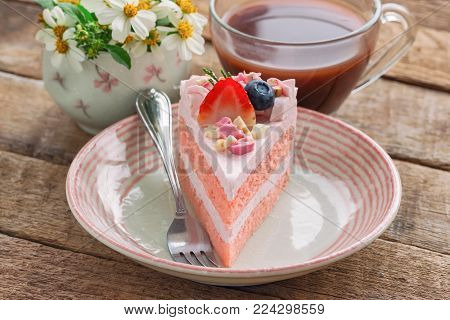 White chocolate strawberry yogurt cake decorated with fresh fruits and chocolate chunk. Sweet pink cake on wood table with copy space. Delicious and sweet pink cake for Valentines or birthday party. Homemade bakery concept. Sweet strawberry cake.