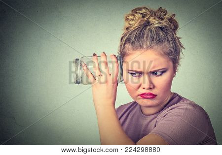 Nosy woman with glass jar carefully listens to gossip conversation behind the wall. Human face expression