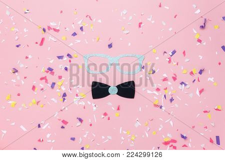Table top view aerial image of beautiful carnival mask or photo booth props background.Flat lay glasses & gentleman bow tie on modern rustic pink paper at office desk studio.space for creative design.