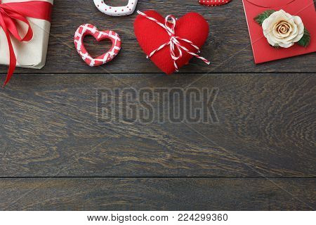 Table top view aerial image of decoration valentine's day background concept.Flat lay red heart with essential accessory seasonal on modern rustic brown wooden.space for creative mock up & template.
