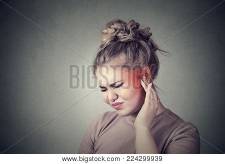 Tinnitus. Closeup up side profile sick female having ear pain touching her painful head colored in red isolated on gray background