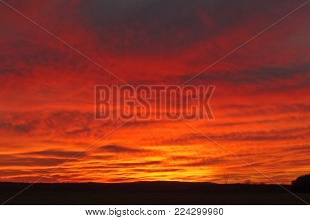 Evening sky. Low hovering clouds. From underneath it is illuminated by the red light of the sun hiding behind the horizon, giving them an intense red color.
