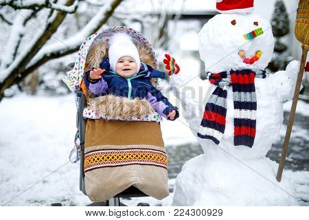 Cute little beautiful baby girl sitting in the pram or stroller on winter day with snow and snowman. Happy smiling child in warm clothes, fashion stylish baby.
