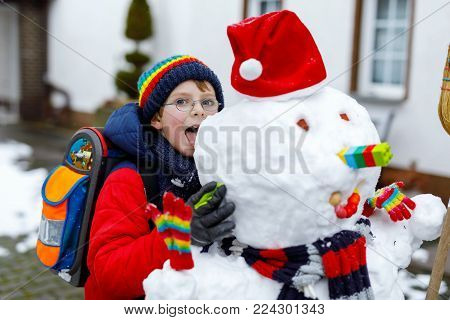 Little school kid boy in colorful clothes, with glasses and backpack having fun with snowman after elementary school end. Child playing with snow on winter day.