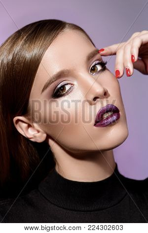 Portrait of an attractive girl with bright makeup and violet lips. Styling for long hair. Modern youth fashion.