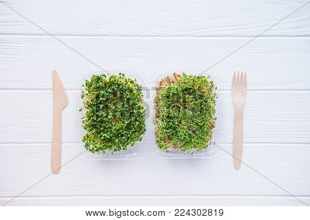 Top view plastic boxes with fresh organic sprout micro greens and wooden cutlery on the white table. Healthy Raw diet food concept. Copy space for text. Selective focus