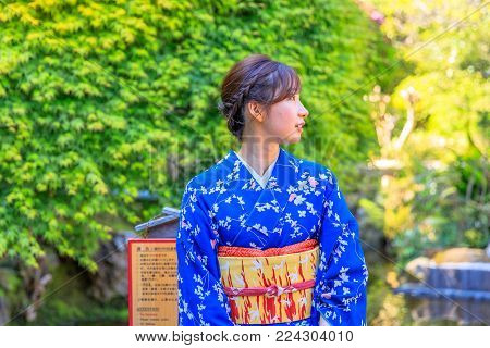 Kamakura, Japan - April 23, 2017:Take-Dera Temple garden in Kamakura with one single woman in classical Japanese kimono on green springtime season foliage background. Japanese experience and lifestyle