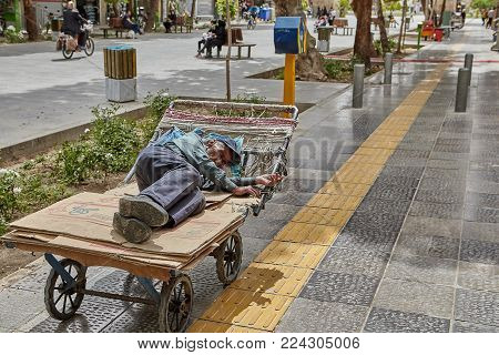 Isfahan, Iran - April 24, 2017: Iranian elderly homeless man is sleeping on a cart on a busy street.