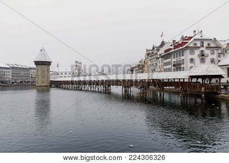 A historic wooden bridge across the river, a landmark in Lucerne, Switzerland.