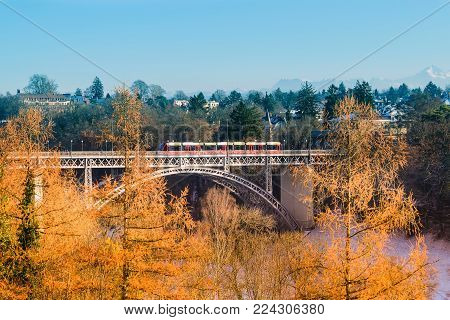 The train is sailing on a river bridge with a back view of the Alps in Bern, Switzerland.