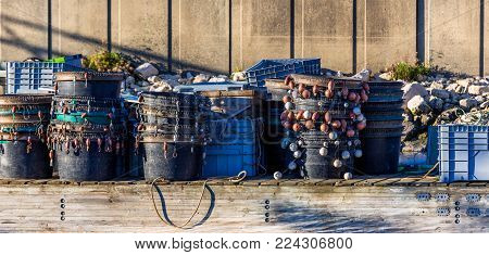 Lobster Traps Standing On A Pier Prepared For Fishing With Ropes And Buoys