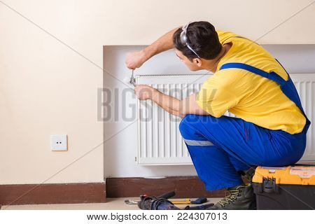 Young repairman contractor repairing heating panel