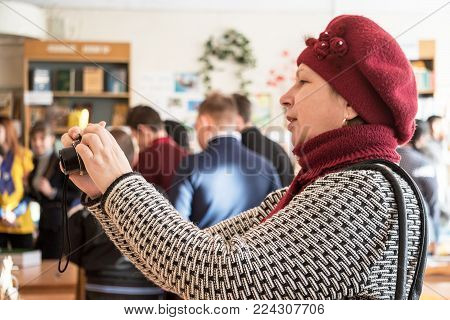 CHAPAEVSK, SAMARA REGION, RUSSIA - JANUARY 26, 2018: College in Chapaevsk city. Visitors to the exhibition of works of students at the College of the city of Chapaevsk. A woman photographs