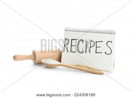 Flour for bread, kitchen utensils and notebook on white background