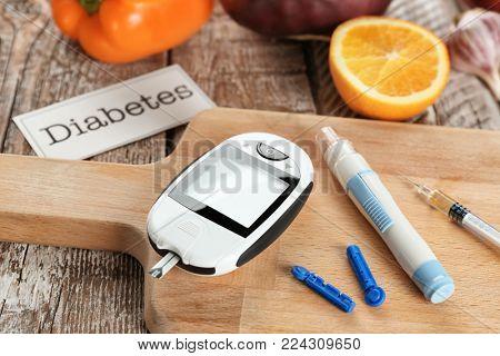 Digital glucometer, lancet pen and syringe on table. Diabetes diet