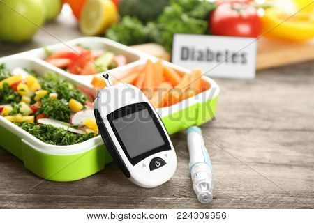 Digital glucometer, lancet pen and lunch box with vegetables on table. Diabetes diet