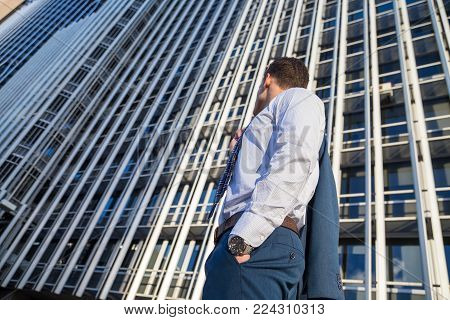 Back View Of Businessman In Classy Suit Holding His Jacket On Background Of Modern Office Skyscraper