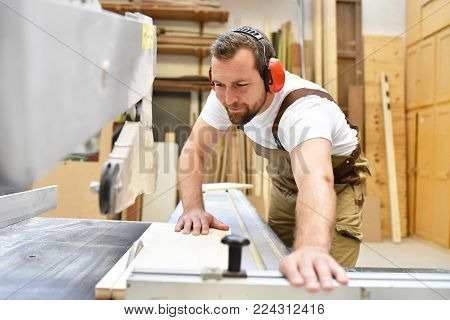friendly carpenter with ear protectors and working clothes working on a saw in the workshop poster